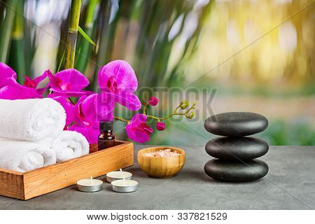 Hot Spa Stones Set For Massage Treatment, Orchid Flower, Towels, Candles And Sea Salt On Green Backg