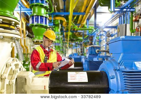 Engineer looking at a checklist during maintenance work in a large industrial engine room