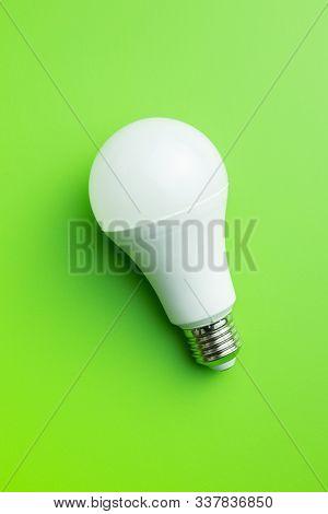 Energy saving light bulb on green background. LED light bulb. Top view.