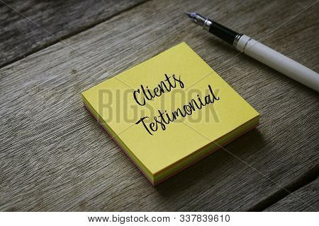 Pen And Yellow Sticky Notes Written With Clients Testimonial On Wooden Background.