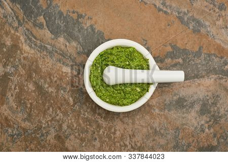 Top View Of Pesto Sauce In Pounder On Stone Surface