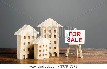 Wooden Figures Of Residential Buildings And An Easel Sign Labeled For Sale. Buying And Selling Real