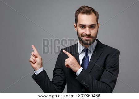 Confident Young Bearded Business Man In Classic Black Suit Shirt Tie Posing Isolated On Grey Wall Ba