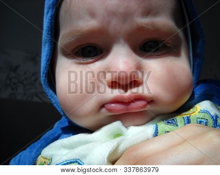 The Little Child Pouted And Frowned. A Hood Of Blue Plush Overalls Is Put On His Head. The Child Has