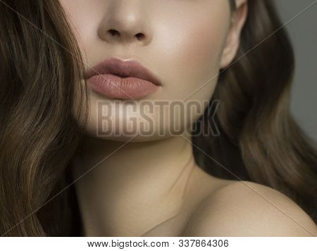 Close-up Of Woman's Lips With Fashion Natural Beige Lipstick Makeup. Macro Sexy Pale Lipgloss Make-u