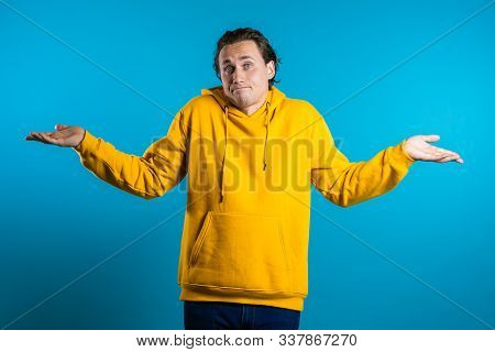 Young Handsome Unsure Guy In Yellow Hoodie Shrugs His Arms, Makes Gesture Of I Dont Know, Cant Help
