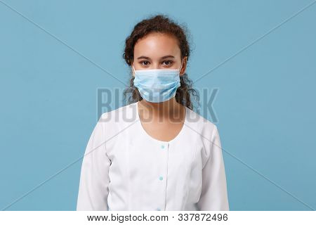 African American Doctor Woman Isolated On Blue Background. Female Doctor In White Medical Gown With
