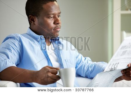 Image of young African man reading news in the morning