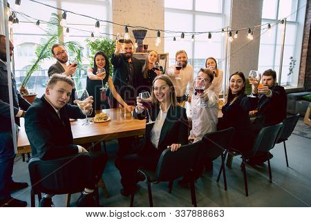 Happy Co-workers Celebrating While Company Party And Corporate Event. Young Caucasian People In Busi
