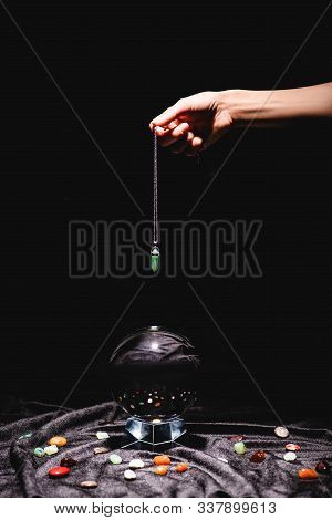 Cropped View Of Fortuneteller Holding Stone Above Crystal Ball With Fortune Telling Stones On Black