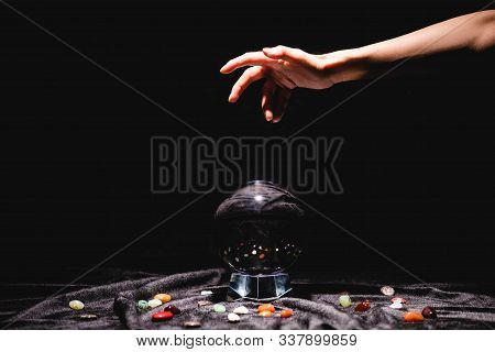 Cropped View Of Fortuneteller Hand Above Crystal Ball With Fortune Telling Stones On Black Velvet Cl