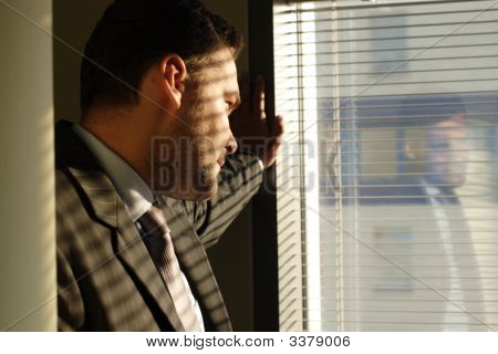 Man Looking Through Window Blinds