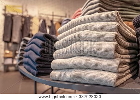 A Stack Of Clothes In The Store, Pullovers And Sweatshirts Nicely And Neatly Stacked In Bundles On T