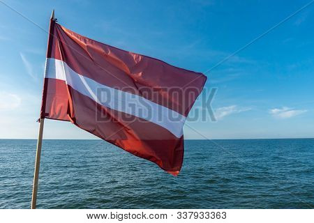 Flag Of Latvia On Blue Sky Background Flying In Strong Breeze Over The Baltic Sea. Latvian National
