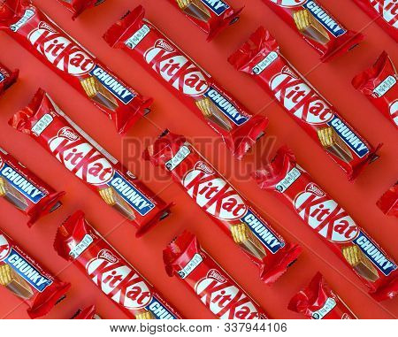 Kit Kat Chocolate Bars In Red Wrapping Lies On Yellow Background Is Now Produced Globally By Nestle.