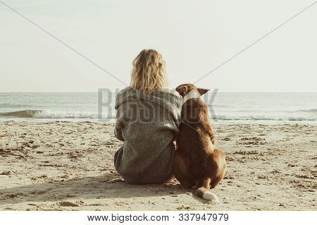 Young Woman Sitting And Hugging Dog On The Beach. Friendship Concept - Woman And Dog Sitting Togethe