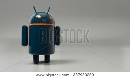 Sindelfingen, Baden Wuerttemberg, Germany - December 6, 2019: A dark Android robot mascot for Google cell phone operating system in front of a gray wall with space.