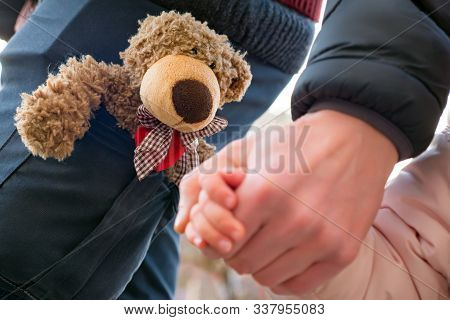 Hands Of Parent And Child Outdoor Closeup. Father Holds Hands Of Little Girl. Childs And Male Hands