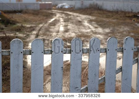 Dirty, Impassable Road Behind The Wooden Gate, Outdoor Shot, Focus In The Foreground