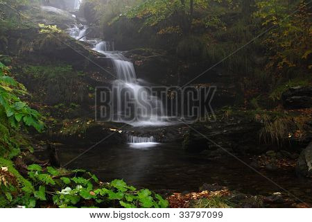 autumn forest waterfall with fog in Czech republic ,Moutains Jesenik,River Borovy potok