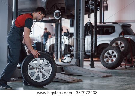 Useful Work. Mechanic Holding A Tire At The Repair Garage. Replacement Of Winter And Summer Tires.