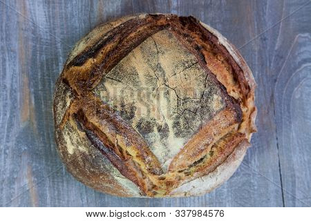 Loafs (or miche) of French sourdough, called as well as Pain de campagne, on display on a wooden table. Pain de Campagne is a typical French huge loaf of bread abiding by the traditional codes. poster