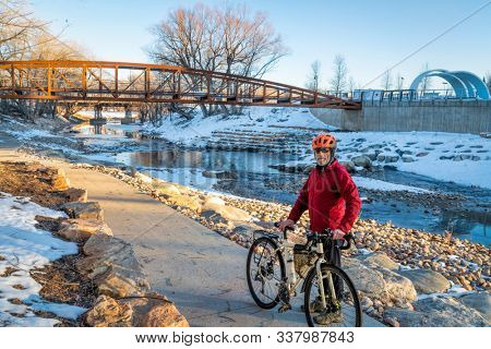 senior male cyclist with a touring bike in winter sunset scenery - Poudre River Trail in Fort Collins, Colorado at downtown whitewater park, recreation and commuting concept