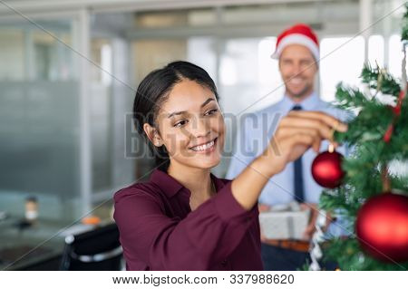 Portrait of smiling latin business woman decorating christmas tree in office. Happy middle eastern woman decorating tree for christmas holiday. Multiethnic people celebrating xmas holiday at work.