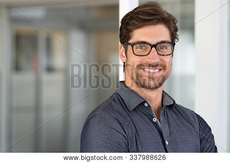Portrait of handsome businessman standing in modern conference room. Happy young business man looking at camera with copy space. Portrait of successful smiling guy in office wearing eyeglasses.