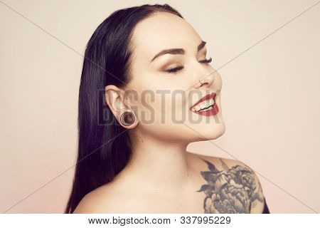 Portrait Of A Brunette With A Tunnel In Her Ears, And A Pierced Nose. Beautiful Duvushka With A Prof