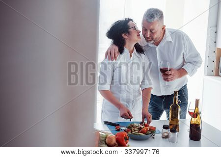 Unshaved Husband Giving Some Love. Man And His Wife In White Shirt Preparing Food On The Kitchen Usi