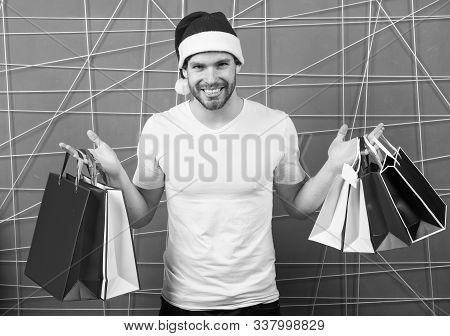 Santa Shopper With Paperbags On Pink Background. Man In Xmas Hat Smile With Colorful Bags. Christmas