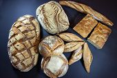 Various French breads, such as baguette, petits pains and loafs of sourdough, called pain de campagne, on display on a table. These breads are symbol of French gastronomy, made of yeast called levain. poster