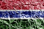 Gambia flag depicted in paint colors on shiny crumpled aluminium foil closeup. Textured banner on rough background poster