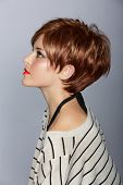 profile of a beautiful woman with red lips and short feathered red hair in modern bob over studio background poster
