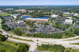 Aerial view of an suburban office park with parking lot and adjacent parkway.