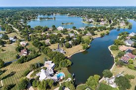 Large community with luxury homes surrounded by lakes in a suburban location.