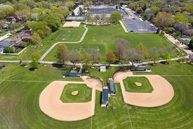 Aerial view of a large playfield in a suburban neighborhood with ballfields, tennis courts, and soccer fields.