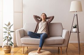 Finally Weekends. Millennial Girl Relaxing At Home On Couch, Enjoying Free Time, Empty Space