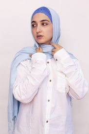 Elegant Muslim Woman In White Shirt And Bright Blue Hijab. Stylish Iranian Girl In Muslim Clothing.