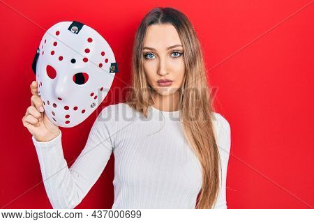 Young blonde girl holding hockey mask thinking attitude and sober expression looking self confident