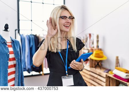 Young blonde woman working as manager at retail boutique smiling with hand over ear listening an hearing to rumor or gossip. deafness concept.