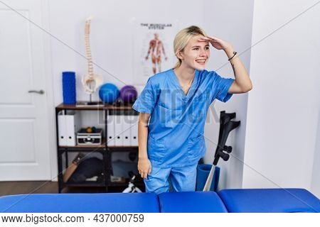 Young physiotherapist woman working at pain recovery clinic very happy and smiling looking far away with hand over head. searching concept.