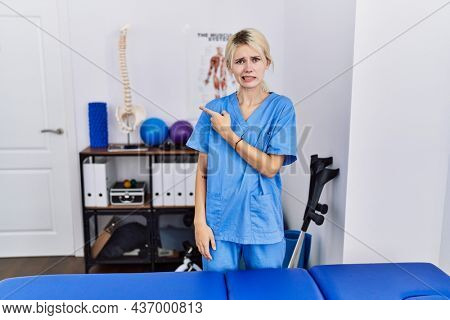 Young physiotherapist woman working at pain recovery clinic pointing aside worried and nervous with forefinger, concerned and surprised expression