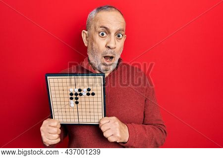 Handsome mature man holding asian go game board in shock face, looking skeptical and sarcastic, surprised with open mouth