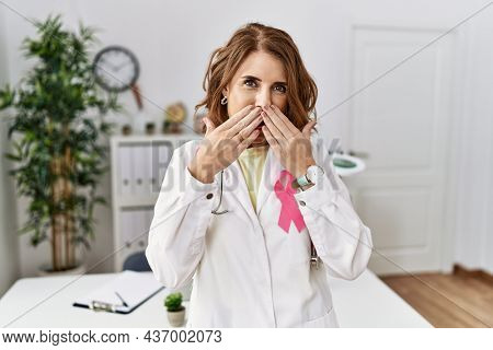 Middle age doctor woman wearing pink cancer ribbon on uniform laughing and embarrassed giggle covering mouth with hands, gossip and scandal concept