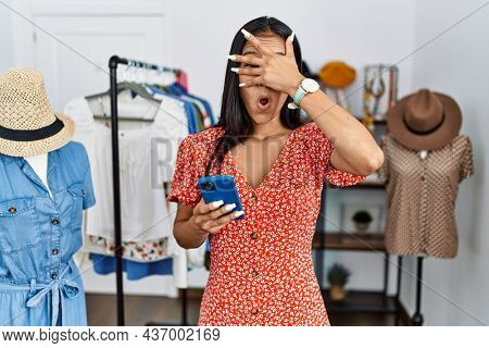 Young hispanic woman working at retail boutique using smartphone peeking in shock covering face and eyes with hand, looking through fingers with embarrassed expression.