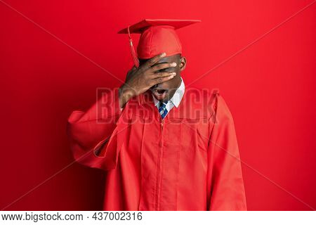 Young african american man wearing graduation cap and ceremony robe peeking in shock covering face and eyes with hand, looking through fingers with embarrassed expression.
