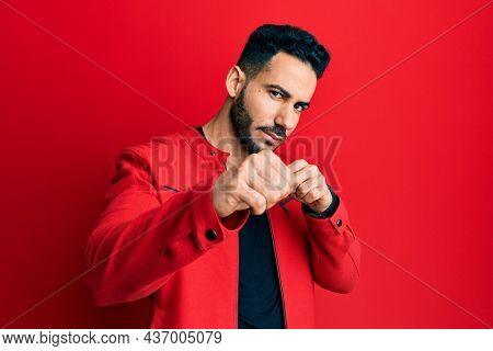 Young hispanic man wearing red leather jacket punching fist to fight, aggressive and angry attack, threat and violence