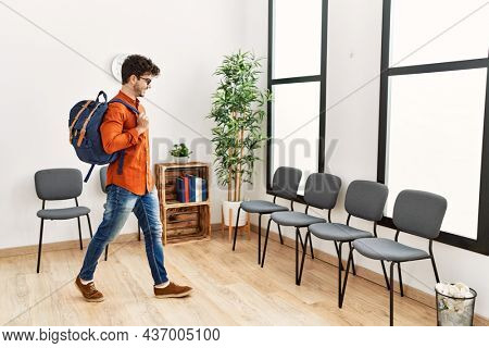 Young hispanic man smiling confident wearing backpack at waiting room